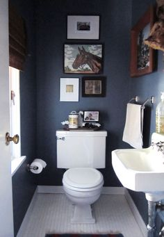 Navy bathroom with artwork hung vertically.  The arrangement draws your eye up and makes the room seem larger!