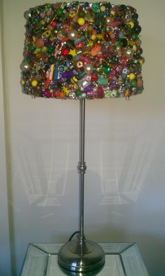 An old lampshade transformed by beads, brooches etc