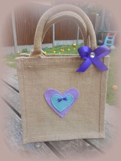 Small jute bag decorated with felt hearts and bows