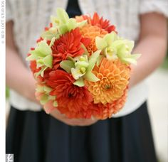 Adding a pop of color to their blue dresses, the bridesmaids carried bright bouquets of tangerine dahlias and green cymbidium orchids.