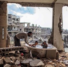Gaza bath - © Emad Samir Palestinian father bathing his daughter and niece in their destroyed home.EMAD SAMIR Winner photographer of the year, Sharjah Award 'Bath Time Gaza' 2016 Sharjah, War Photography, Documentary Photography, Street Photography, Faith In Humanity, Bath Time, Documentaries, Bathing, Around The Worlds