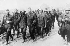 British prisoners, most of them wounded, being escorted by German guards to a dressing station after the attack at the Oppy Wood, 1 May 1917. Private T. Spencer is shown smoking a pipe.