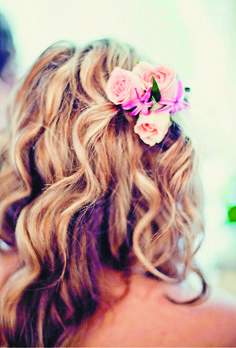 A fresh flower in the hair for the beautiful bride.