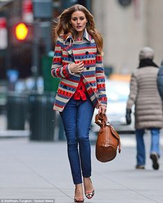 Getting chilly: Olivia began to look a little cold after the long shoot, which including modeling a light brown leather handbag