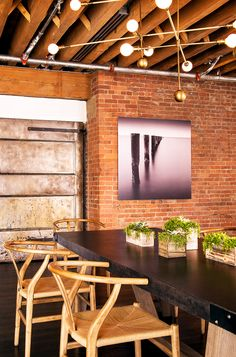 Brick wall in living and dining space with modern light fixture above table // industrial loft