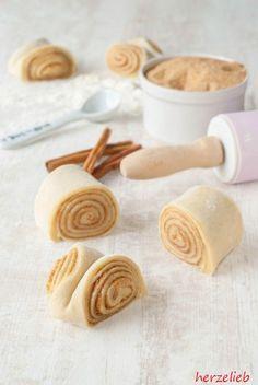 Teig ausrollen, mit Butter bestreichen, aufrollen und kleine Trapeze schneiden. Dann in der Mitte parallel zu den Schmittflächen eindrücken und backen. Das Rezept ist kinderleicht