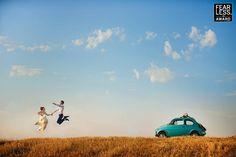 """Collection 28 Fearless Award by ANDREA CORSI (Italy)  http://www.fearlessphotographers.com/photographers.cfm?photogID=2220&andrea-corsi  """"A sunny blue sky and fresh gold field form a clean canvas that lets us zoom in on the story: the cheerful turquoise car and the couple jumping for joy. Their mirrored composition at either end of the frame makes the viewer's gaze linger, bouncing back and forth between the car and the exuberant bride and groom."""""""