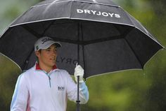 Dominic Foos of Germany shelters from the rain during the weather delayed first round of The Nelson Mandela Championship at Mount Edgecombe Country Club on December 12, 2013 in Durban, South Africa.