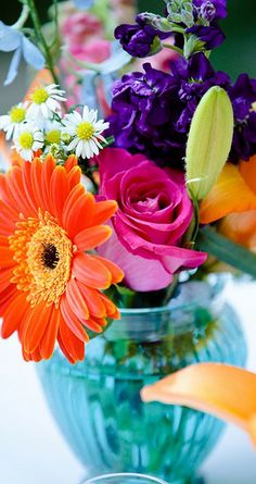 bright flower centerpiece with orange gerberas, hot pink roses and more.