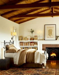 comfy bedroom with beamed ceiling + fireplace