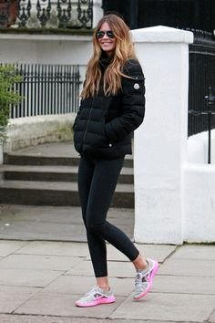 Elle in a Puffer jacket, black tights & pink & gray athletic shoes.