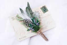 A stylish modern boutonniere composed of preserved eucalyptus and juniper, artificial dusty miller, and elegant feathers. The stem is wrapped in twine for a natural look. A corsage pin is included for attaching to the lapel. Sold separately. Price is for ONE boutonniere. MEASUREMENTS Approximately 14cm / 5.5 in tall. SHOP See more beautiful boutonnieres here: https://www.etsy.com/shop/NoonOnTheMoon?section_id=15464147  POLICIES Please read my shop policies before placing an order…