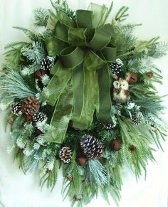 "This beautiful Christmas Wreath sets on a artificial Christmas Pine Wreath base. The wreath is embellished with lots of Christmas Pines, Pine Cones . The wreath is accented with six rustic Jingle Bells and a cute owl. The wreath measures 31"" (L), 28"" (W)"