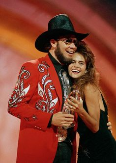 """Hank Jr gets a hug from a presenter as he accept his second """"Entertainer of the Year"""" award at """"The 22nd Annual of Country Music Association Awards"""" show on October 23, 1988 in Nashville, Tennessee."""