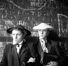 Teddy Girls gang, UK 1954. Style characterized by Eduardian coats, velvit lapels, rolled jeans, espadrille flats, straw boating hats and fancy clutches.