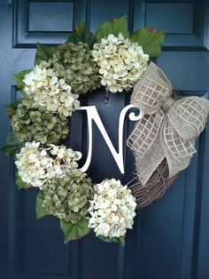 The Olivia wreath will make a beautiful addition to your front door. It has sage and cream hydrangeas attached to a grapevine wreath and tied with a burlap and burlap net bow. Monogram letter is pictured in cream... Choose the initial monogram you would like to make it personal. Finished wreath measures approximately 20 in diameter.  Each flower, bow and letter is wired and glued to the wreath for optimum durability
