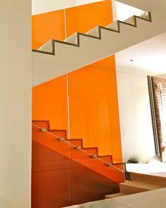 Garde-corps en verre feuilleté trempé orange installé par Vitralux Bradtke S.à r.l. chez un particulier. Le garde-corps est constitué de 4 volumes posés avec des attaches en inox Ø 50 mm. et s'étend de la cave jusquà l'étage +1 de la maison.