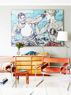Leather and metal chair in living space with graphic art and light wood console table