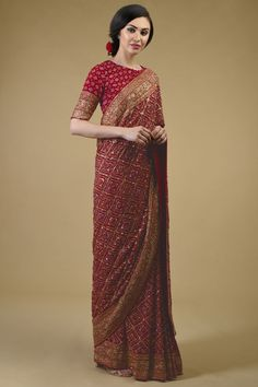 From our heritage bridal collection, this red Masterpiece saree is a coming together of exotic Banarasi Zari hand weaving, handcrafted exquisite Gujarati Bandhej and intricate rich heritage Zardozi hand embroidery. Take a close look at the stunni Indian Gowns Dresses, Indian Fashion Dresses, Dress Indian Style, Indian Designer Outfits, Designer Dresses, Silk Saree Blouse Designs, Indian Bridal Outfits, Saree Trends, Stylish Sarees
