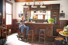 """When the barn was in the design stage, Sheryl planned to have a simple writing room upstairs, but once the room was soundproofed, it became a full-blown studio. """"It's ideal because I'm a single mom—I can go to work just down the driveway,"""" she says. Downstairs, Sheryl created a saloon and filled the walls with her impressive collection of antique signs."""