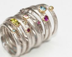 Selection of rings in sterling silver, 18 carat yellow gold, platinum, various coloured diamonds, peridot, ruby.
