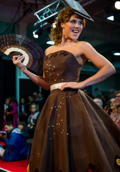 """""""Eternal Diamond,"""" an A-line dress hand-painted with 40 pounds of Lindt chocolate. It's adorned simply along the hem with chili and orange segments, flavors used in speciality Lindt chocolate bars. The fan and hat are also crafted from chocolate, of course.  Showcased at the Salon du Chocolat, the world's largest chocolate show in London October 18-20, 2013."""