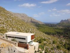 Casa 115 is a contemporary residence that overlooks the a gorgeous valley framing the Saint Vicenc bay. It was designed and built by architect Miquel Angel Lacomba and is located in Mallorca, Spain.