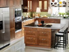 Lovely ikea kitchen.  Akurum Adel medium brown doors & panels, wood effect cabinet bases.  Black Appliances (no stainless), Light Green Walls, Ivory Stone Effect Counters.