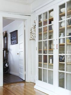 French doors on bookcases in the livingroom. Bifolds flanked by 'press-to-open' (no visible hardware) plain doors that look like walls & provide hidden storage for no so pretty stuff. French doors would display shelves of books, TV, pottery, etc. Interior And Exterior, Interior Design, Built In Cabinets, Glass Cabinets, Built In Bookcase, Built Ins, Old Houses, My Dream Home, Home Projects