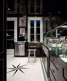 Glamorous black glossy kitchen with black kitchen cabinets, mirrored countertop & backsplash.