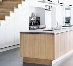 great use of space below a stair well A kitchen in Scandinavia, via Emma's Design Blogg.
