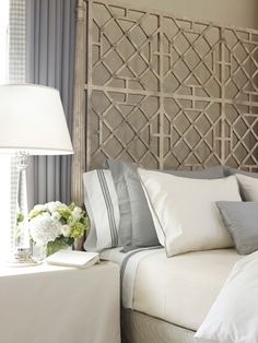 Flank a faux bamboo/chinoiserie/hollywood regency screen with curtains, perhaps a lighted valance for beautiful focal point headboard.  For chic on the cheap, headboard upholstered with faux bamboo screen printed fabric or even framed out wallpaper on wall behind bed