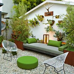 This small outdoor space in Venice, California, lives large with seating edged by planter boxes, natural paving underfoot, and mounted staghorn ferns that mingle gallery-style with mounted antlers.