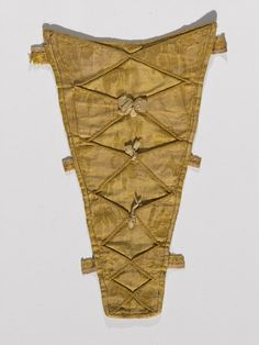 Stomacher, probably England or North America, ca. 1750-1755. Golden silk damask with applied decoration.
