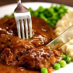 Salisbury Steak cutting gravy peas mashed potatoes