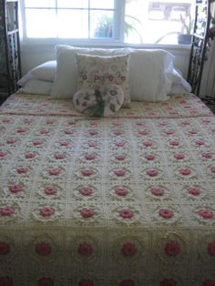 This is a queen size hand crocheted cotton thread bedspread coverlet. It has 270 squares in ecru. Within each square is a delicate raised pink rose. The simple finished trimmed border is also in pink to compliment the roses.      $650