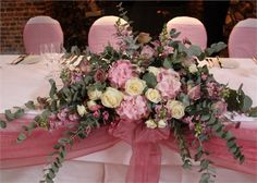 """A lovely arrangement of flowers, useful for the top table, I really like the colour and different sizes of the flowers """"A soft trailing traditional top table arrangement of roses and eucalyptus... This could  be used as a ceremony arrangement and moved to the top table afterwards"""""""