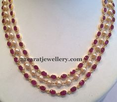 Two lines of ruby strings attached with south sea pearls chain and merged with designer two side motifs. 22 carat gold metal used in i...