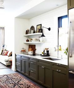 Inside a Toronto Row House With Elegant, Eclectic Style via @domainehome Kitchen Olive cabinets