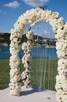 An archway wrapped with white roses with a curtain of crystal beads has a dazzling effect at an outdoor wedding.