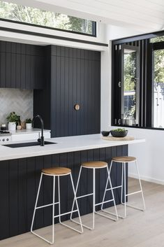 "The dark kitchen cabinetry is a nod to the exterior, ""as the pattern of the shiplapped cladding informed the grooves of the kitchen joinery,"" says the firm. #dwell #modernaustralianhomes #modernhomerenovations #modernkitchenideas"