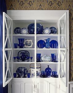 Dining Room Cabinet filled with cobalt blue glassware, transferware and Chinese porcelain.  Source: House Beautifu. Image found here: www.housebeautiful.com/decorating/colors/classic-blue-decor#slide-8
