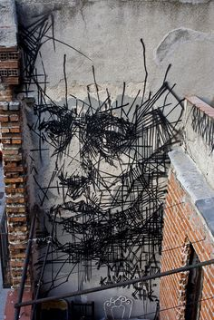 The artist uses pipes from a street to create a line effect bringing out the picture of the persons face.