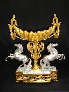 Diana  -  A bronze trophy with 2 horses, gold and sometimes engraved bronze (bronze dore), White Marmorund silver. Inlays, carvings and reliefs. Louis XVI style. The oval bowl trophy shaped like a large pearl oyster, with delicate tendrils decoration. On the sides decorated rocaille and C Henkel conch shell is supported at its center by a balustrade with capitals and carvings, decorated with curly branches, flanked by two silver studs. Base of white, French marble encased in a broken frame…