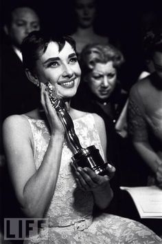 """Audrey Meets Oscar  Audrey Hepburn affectionately holds the Oscar she won for her performance in """"Roman Holiday"""" at the Academy Awards ceremony."""
