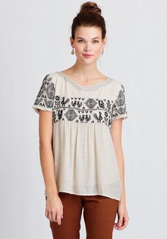 This stunning beige blouse is rendered in a soft gauzy fabric and features an empire silhouette.