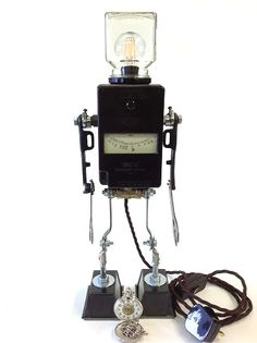 robot light by www.pbrobots.com this is a handmade robot light from vintage materials. the body is a vintage Bakelite test meter with spanners for arms and legs it you would like to buy this guy you can get him for £265.00 from my web site. robot sculptures assemblage art SOLD