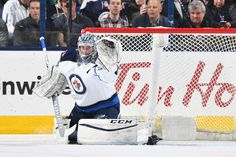 COLUMBUS, OH - APRIL 6: Goaltender Eric Comrie #1 of the Winnipeg Jets makes a glove save during the first period of a game against the Columbus Blue Jackets on April 6, 2017 at Nationwide Arena in Columbus, Ohio. (Photo by Jamie Sabau/NHLI via Getty Images)