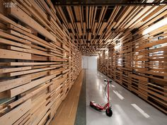 Varying sizes of naturally finished boards are secured to vertical posts as wall dividers.  This idea could be repurposed to create a dimensional wood wall over the long paneled wall.  The wall behind could be painted black, white, or a bright accent color.  [Image courtesy of: 30 Simply Amazing Spaces For Work | Projects | Interior Design]