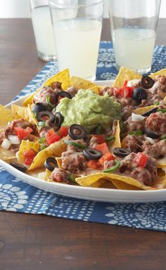 Cheesy Beef Nachos — Exactly what you're looking for in nachos: chips, ground beef, melty cheese, guac, salsa, fresh tomato and a jalapeño zap. Perfect game-day (or any day) food.